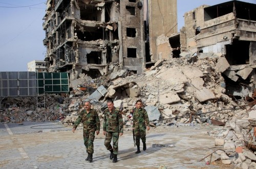 Syrian army soldiers walk through government-held Aleppo in 2015 (AFP)