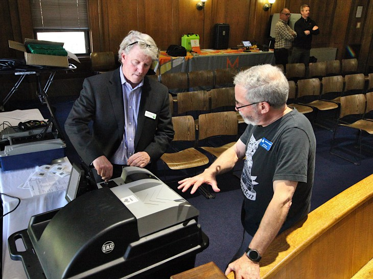 Keith McGinnis (left) represented Unisyn Voting Systems. He's talking to Hal Turner, member of Monroe County's election board. (Dave Askins/Beacon)