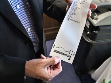 Keith McGinnis holds the printed receipt-style ballot produced by Unisyn's system. (Dave Askins/Beacon)
