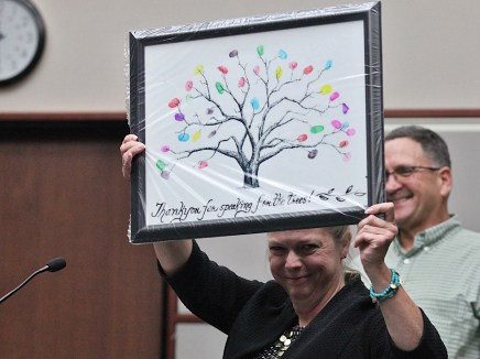 Susan Coleman holds aloft a card made by the first- and second-graders at Project School for Lee Huss in honor of his retirement. (Dave Askins/Beacon)