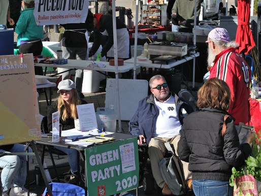 Green Party organizer Randy Paul talks with a farmers market patron on a recent Saturday. Amanda Sheridan staffs the table. This fall the Green Party (left) has tabled at Information Alley at Bloomington's farmers market. (Dave Askins/Beacon)