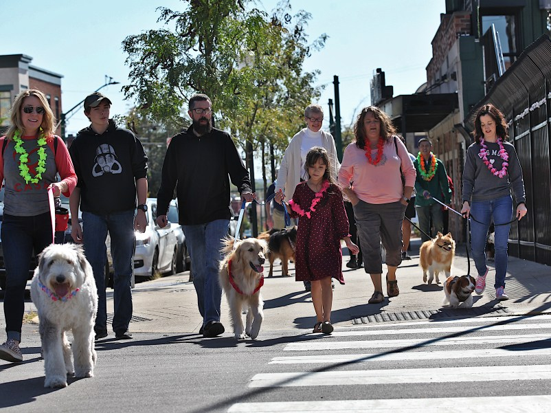 Pup Parade for Jordy's fifth birthday party. He's the golden retriever flanked by David Arthur and Olivia Bounds who are holding his leash. (Dave Askins/Beacon)