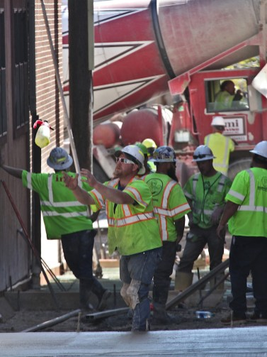 A crew from E & B Paving work on the alley between 7th and 6th streets on the block between Washington and Walnut on Oct. 16, 2020. (Dave Askins/Square Beacon) [This worker's feet stayed in the excavated portion of the site and he maintained control, establishing possession, so it was ruled a catch by officials on the scene.]
