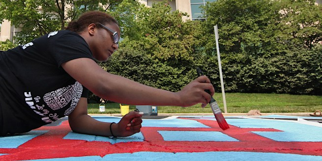 IU public health student Brittany Dobbins helps helps paint the Black Lives Matter mural on the campus street to be renamed Eagleson Avenue. (July 5, 2021)