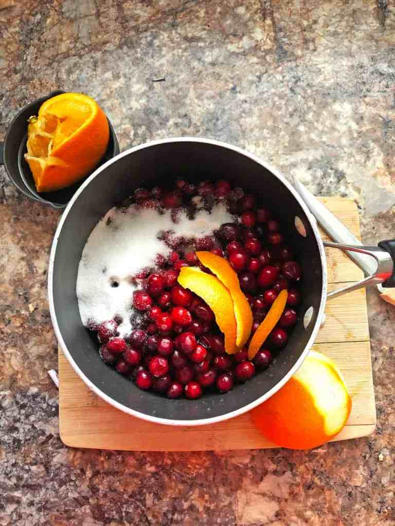 A pot of cranberries, sugar, and orange peel