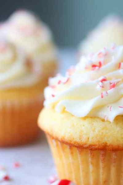 white cupcakes with frosting with crushed candy canes