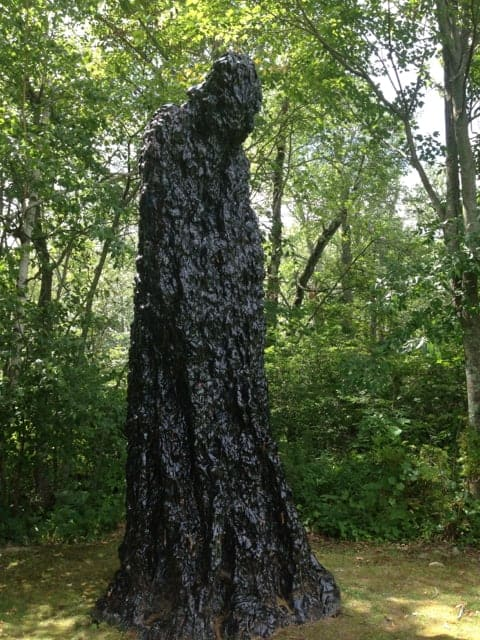 A hooded figure stands like a weathered tree trunk. Photo by Kate Abbott