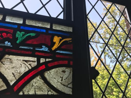 An inset stained glass panel, a Grisaille from France, shines among diamond panes. Photo by Kate Abbott