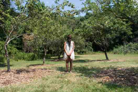 Allison Janae Hamilton - Dollbaby standing in the orchard at midday. Courtesy of the artist