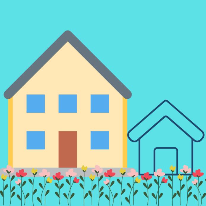 Woning met bijgebouw en gazon met bloemen