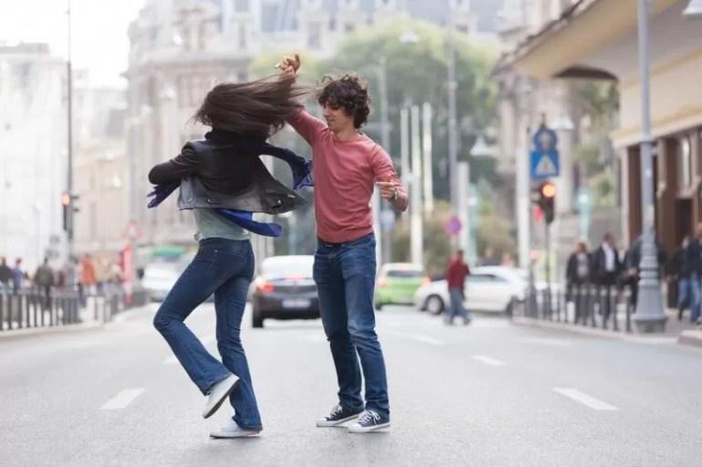 couple dancing in the street wearing casual wear