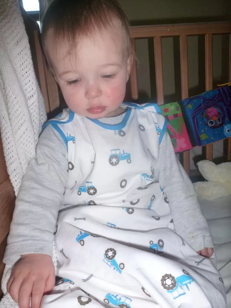 toddler waking up from sleep in a tractor grobag