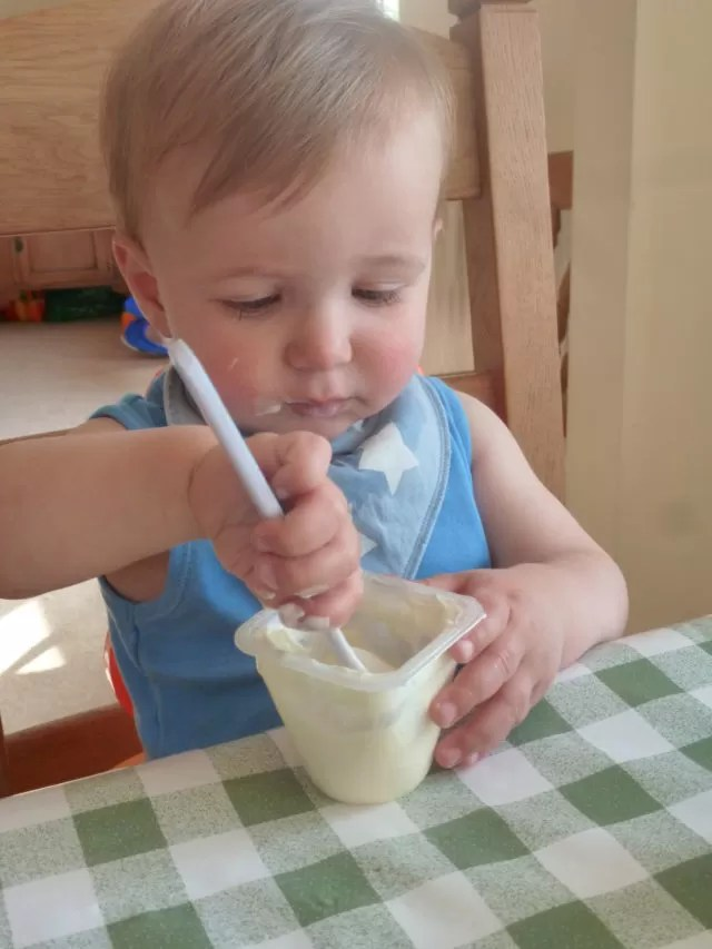 toddler sitting at table eating yoghurt in a blue vet top