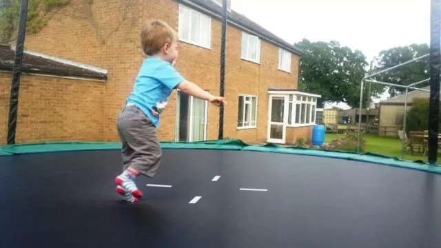 toddle bouncing on garden trampoline
