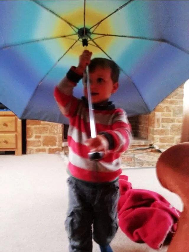 toddler playing with open ombre colour umbrella (1)