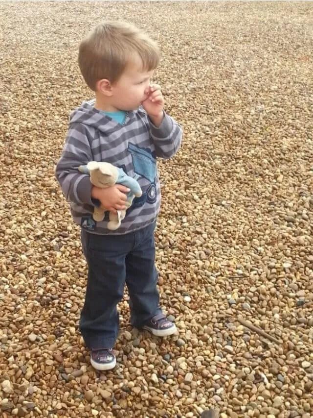 toddler walking holding peter rabbit toy