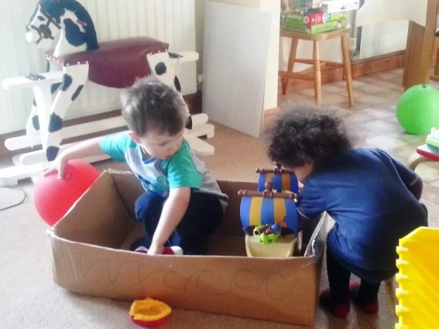 toddlers playing with a boat