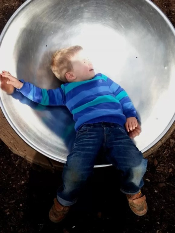 boy in metal bowl playground equipment