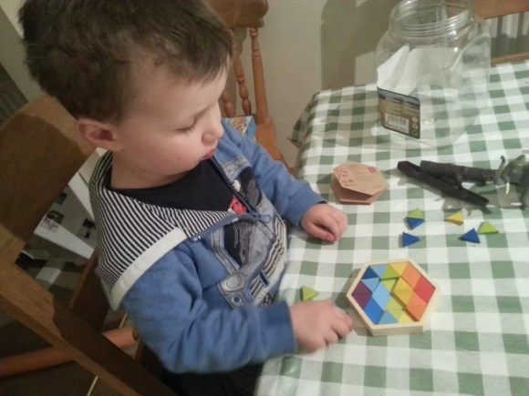 toddler playing a colour geomix triangle puzzle