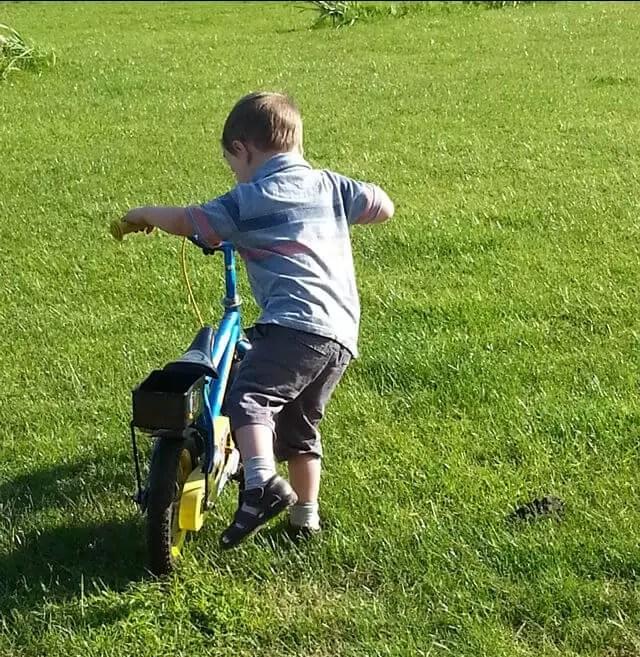toddler-climbing-on-bike.