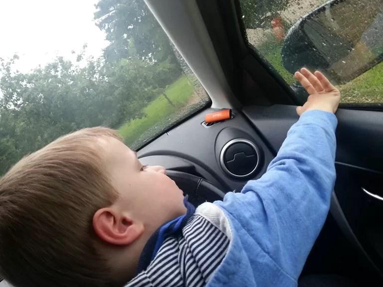 toddler driving the car in rain