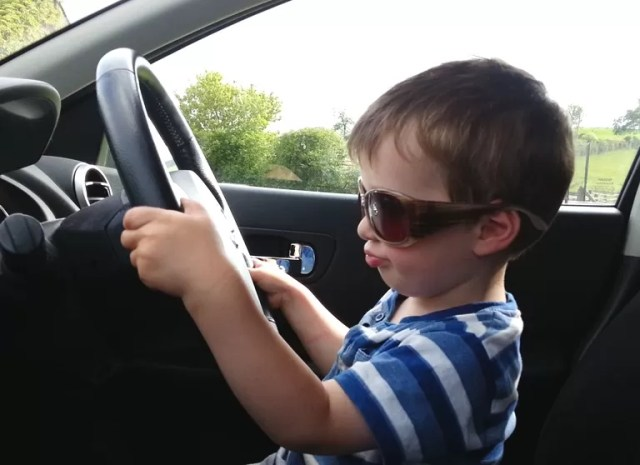 toddler driving a car in sunglasses