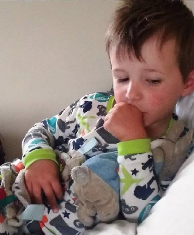 toddler in sleepsuit sucking his thumb