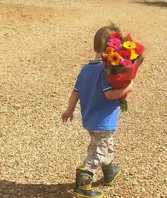 toddler taking-flowers-to-granny