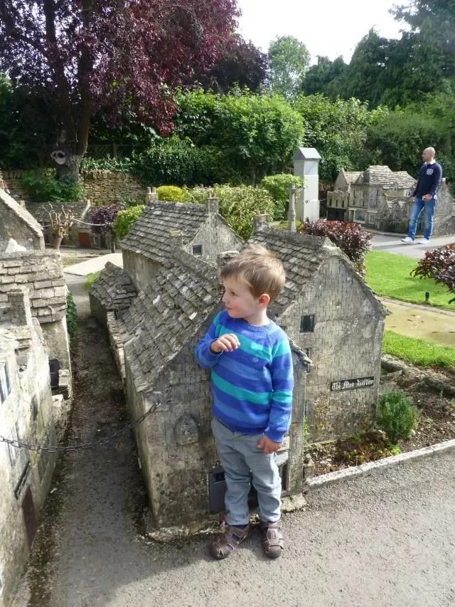 Giant boy measuring himself against a model house