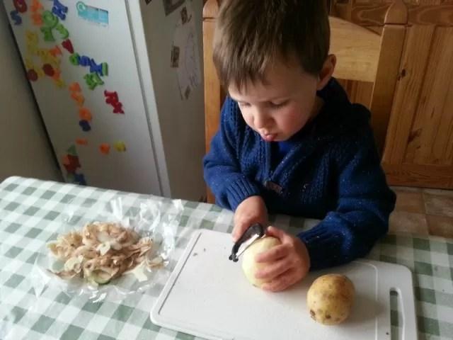 preschooler peeling potatoes