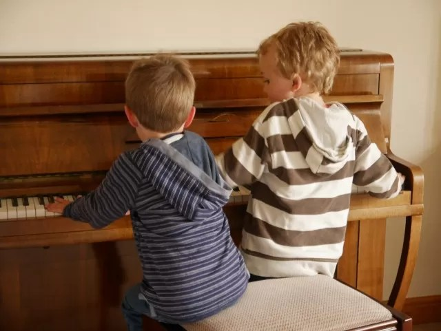 cousins playing piano together