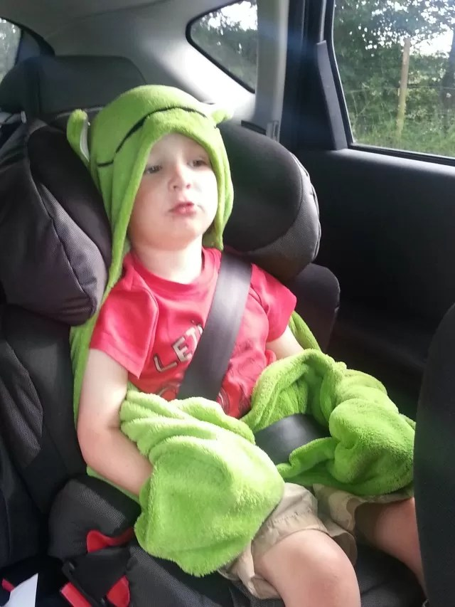 dressed up in his frog blanket in the car