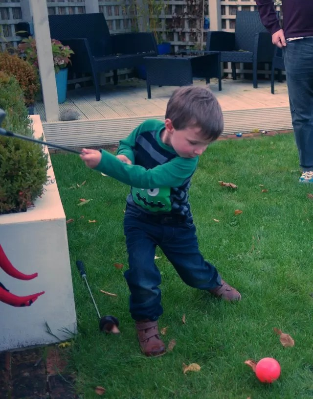 practising his golf swing