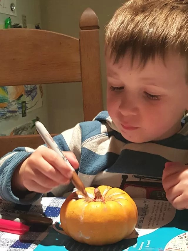 sharpie decorating the pumpkins