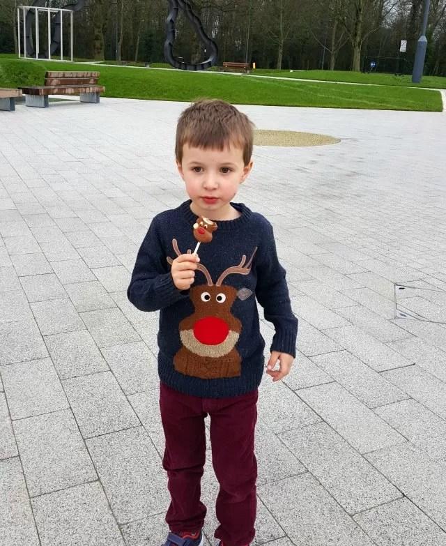 eating his reindeer chocolate lollipop