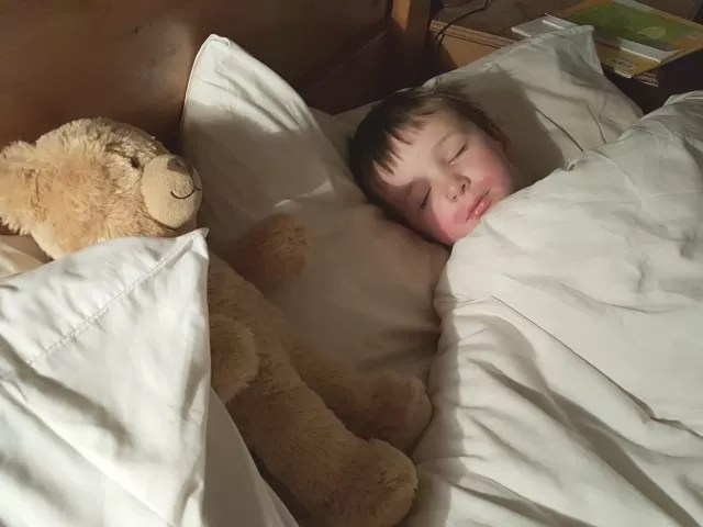 sleeping boy with teddy