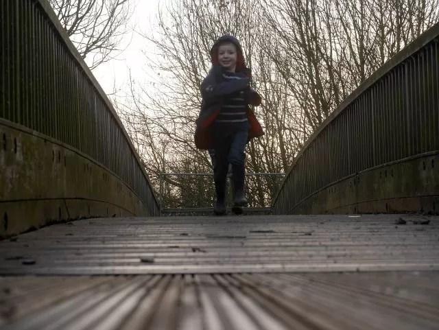 running across the wooden bridge in the park
