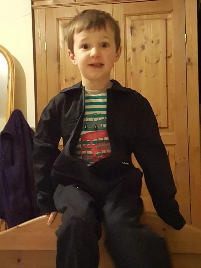 looking scared in his new john deere overalls