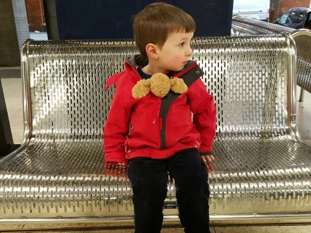 taking his teddy dog for a ride at the station