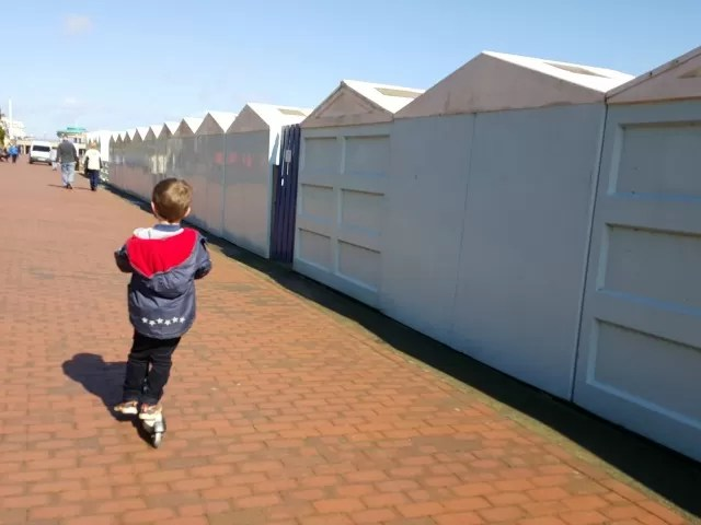 scooting alongside beachhuts at Eastbourne