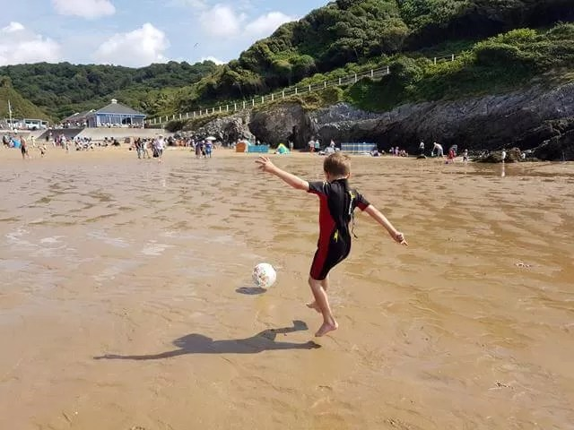 kicking football at caswell bay