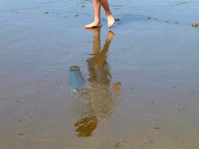 walking on wet sand reflection