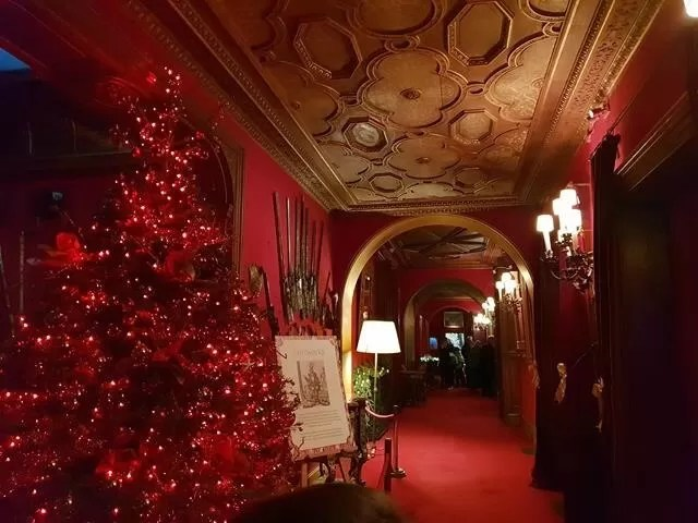 red corridor at waddesdon with red lit up christmas tree