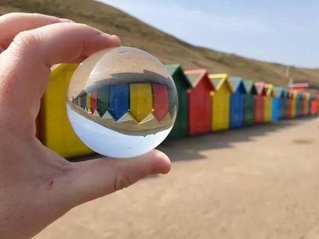 bright coloured beach huts through a lensball