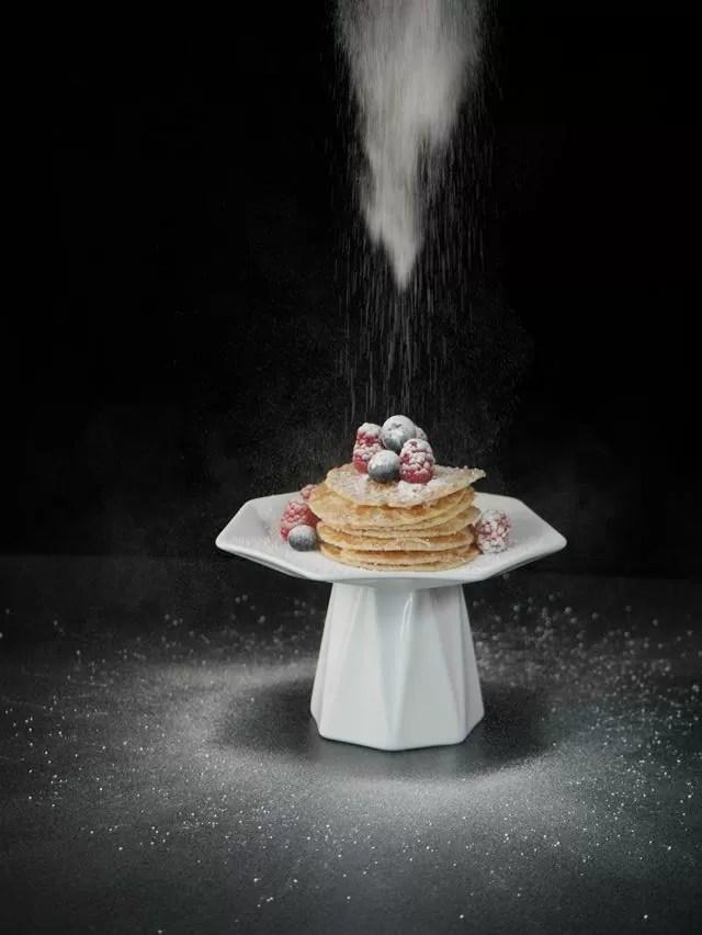 icing sugar tipping on pancakes.