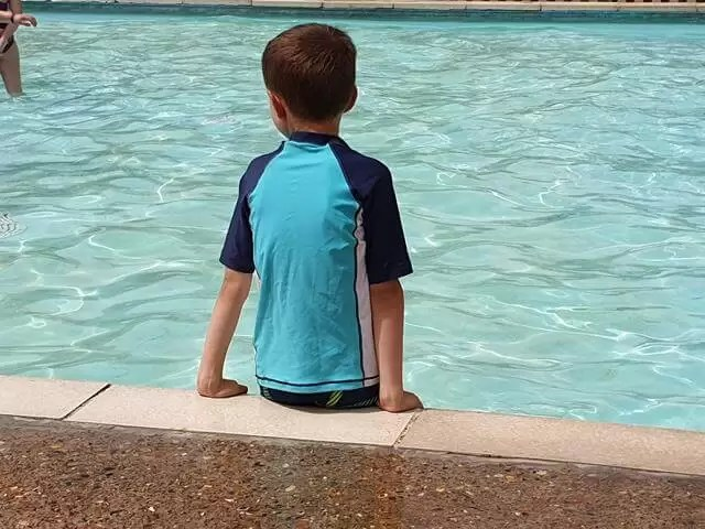 sitting at the side of a paddling pool
