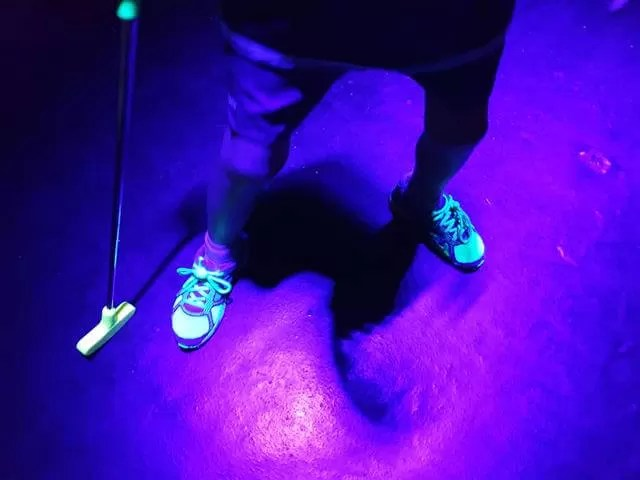 neon lit up trainers and golf club