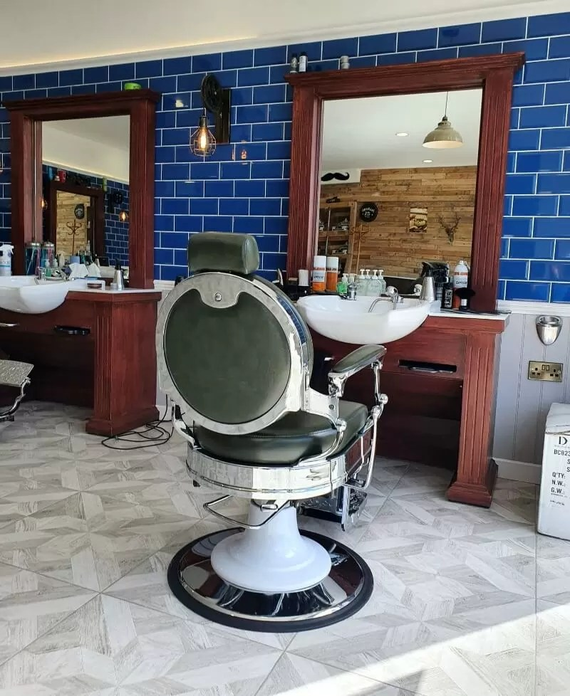 barber's chair in front of mirrors and blue tiles