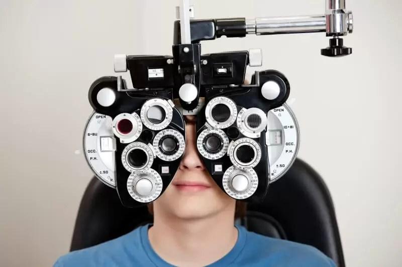 boy in eye test with prescription glasses machine