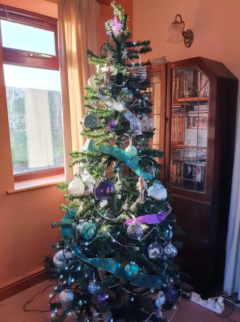 Christmas tree decorated in purple silver and teal green baubles and ribbon